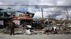 Полицейский регулирует движение на разрушенной тайфуном улице в пригороде Таклобана 14 ноября 2013 года. Число жертв разрушительного тайфуна, ударившего в прошлую пятницу по Филиппинам, в одном только городе удвоилось до 4.000 человек, поставив под сомнение прежние оценки руководства страны. REUTERS/Bobby Yip