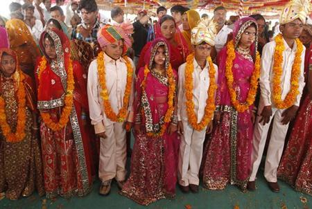 Boys and girls from the Saraniya community wearing garlands pose for pictures after their engagement ceremony at Vadia village in the western Indian state of Gujarat March 11, 2012. REUTERS/Amit Dave