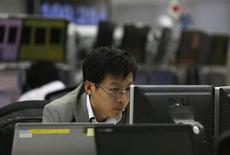 An employee of a foreign exchange trading company looks at monitors in Tokyo November 15, 2013. REUTERS/Toru Hanai