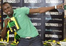 """Jamaican athlete Usain Bolt poses for photographers with a copy of his autobiography, """"Faster than Lightning,"""" at Selfridges in central London September 19, 2013. REUTERS/Neil Hall"""
