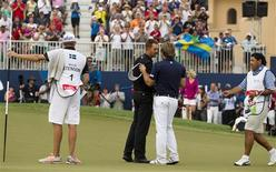 Henrik Stenson of Sweden shakes hands with playing partner Victor Dubuisson (2nd R) of France after winning the DP World Tour Championship in Dubai November 17, 2013. REUTERS/Caren Firouz