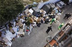 Workers covering essential services remove garbage strewn on a pavement on the 11th day of an indefinite strike by street cleaners in Madrid November 15, 2013. REUTERS/Juan Medina