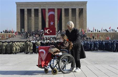 A woman holds the Turkish national flag at the mausoleum of Mustafa Kemal Ataturk, the first president of Turkey and founder of the modern secular state, at Anitkabir in Ankara November 10, 2013. REUTERS/Stringer