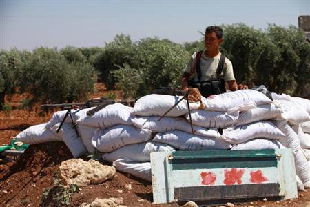 A Free Syrian Army member is seen behind sandbags at a checkpoint during a siege on the Kurdish city of Afrin, which is under the control of the Kurdistan Workers' Party (PKK), in the Aleppo countryside June 30, 2013. REUTERS/Hamid Khatib