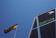 A Spanish flag flies next to the headquarters of Bankia bank in Madrid July 24, 2012. REUTERS/Susana Vera