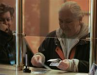 Женщина пересчитывает деньги в банке в Москве 14 ноября 2008 года. Кредитный бум в России и ужесточение денежно-кредитной политики в мире могут грозить российскому банковскому сектору очередным кризисом в 2014 году, и его вероятность выше, чем в Турции, Польше, Чехии, Венгрии, Украине и Израиле, говорится в исследовании Goldman Sachs. REUTERS/Alexander Natruskin