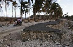 A Hernani, aux Philippines, après le passage du typhon Haiyan. Les pertes économiques liées dans le monde à des catastrophes climatiques n'ont cessé d'augmenter au cours de la dernière décennie pour atteindre 200 milliards de dollars par an, selon un rapport de la Banque mondiale. /Photo prise le 18 novembre 2013/REUTERS/Wolfgang Rattay