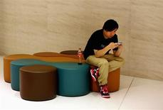 A man looks at his smart phone inside a shopping mall in downtown Shanghai, September 25, 2013. REUTERS/Carlos Barria