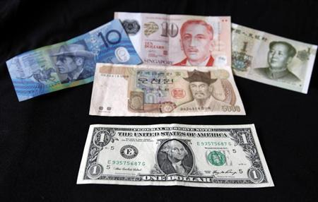 A U.S. dollar note (bottom) is pictured alongside other currencies including (L-R) the Australian Dollar, Singapore Dollar, Korean Won and China's Yuan in this picture illustration taken in Washington, October 14, 2010. REUTERS/Jason Reed