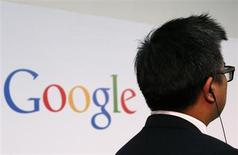 """A man stands in front of a Google logo before a talk titled """"Connecting with the World Empowering Young Entrepreneurs for the New Digital Age"""" by Google Executive Chairman Eric Schmidt (not seen) at the Chinese University of Hong Kong November 4, 2013. REUTERS/Bobby Yip"""