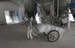 A worker wearing a mask pulls a cart loaded with limestone at a mill in Quzhou, Zhejiang province October 22, 2013. Beijing's strategy to reroute money away from state-owned giants towards smaller firms to help fuel the economic transformation behind its reform plans is less of a success than it may seem on the surface. Picture taken October 22. REUTERS/William Hong