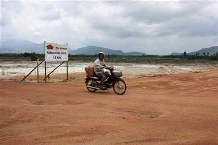 A motorcyclist rides past a dirt road at a site for a billion dollar industrial estate in Dawei district, Myanmar, May 10 , 2012. REUTERS/Khettiya Jittapong