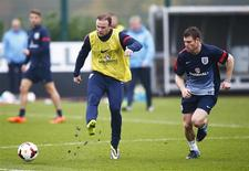 England national soccer team player Wayne Rooney (L) kicks the ball as teammate James Milner chases during a team training session at Arsenal's training facility in London Colney, north of London, November 18, 2013. REUTERS/Andrew Winning