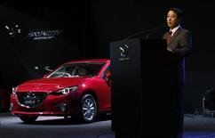 Mazda Motor Corp Chief Executive Officer Masamichi Kogai speaks next to the company's Axela (Mazda 3) compact car during a presentation at the 43rd Tokyo Motor Show in Tokyo November 20, 2013. REUTERS/Toru Hanai