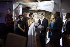 Bride Veronica (4th L) reads a message to her groom Michael (4th R), as they stand underneath a traditional Jewish wedding canopy during their secular wedding ceremony in Tel Aviv November 14, 2013. REUTERS/Nir Elias