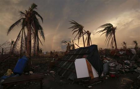 Part of a rainbow appears over the makeshift home of a family at the airport in the eastern Samar town of Guiuan November 20, 2013. REUTERS/Wolfgang Rattay