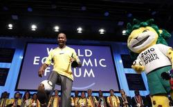 Former South Africa and Leeds United soccer player Lucas Radebe kicks a ball as he is joined by Zakumi, the 2010 World Cup official mascot during the 2010 FIFA World Cup South Africa Davos kick-off at the congress centre in Davos, January 30, 2010. REUTERS/Michael Buholzer