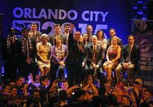 Orlando City SC president Phil Rawlins waves to his wife during a rally for a Major League Soccer official announcement for a expansion franchise agreement with Orlando City Soccer at Cheyenne Saloon. Mandatory Credit: David Manning-USA TODAY Sports