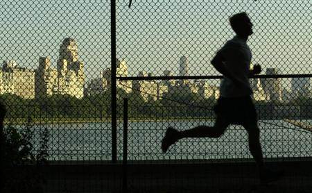 A man jogs along a path around the Central Park Reservoir with the buildings of Fifth Avenue in the backround in New York's famed Central Park, July 15, 2003. REUTERS/Mike Segar