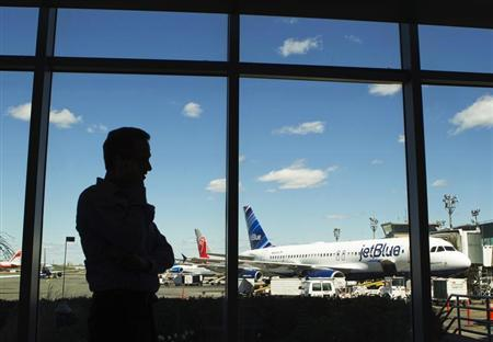 A man talks on his cell phone while looking at a JetBlue Airways plane at LaGuardia Airport in New York April 5, 2012. REUTERS/Lucas Jackson