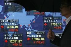Чеовек проходит мимо табло с показателями мировых фондовых индексов в Токио 7 мая 2009 года. Азиатские фондовые рынки выросли за неделю за счет надежд на продолжение стимулирующей программы ФРС, хороших макроэкономических показателей США и локальных факторов. REUTERS/Michael Caronna