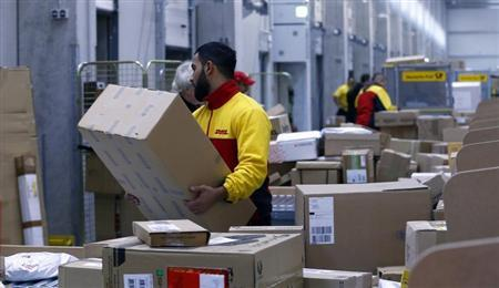 Workers load trucks with parcels at the new distribution centre of the German postal and logistics group Deutsche Post DHL in Berlin November 12, 2013. REUTERS/Tobias Schwarz