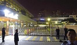 Police and security guards stand outside a gate of a Nokia factory during a protest of around one hundred factory workers in Dongguan, Guangdong province November 20, 2013. REUTERS/James Pomfret