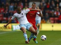 Southampton's Dani Osvaldo (R) tackles West Ham's Winston Reid during their English Premier League soccer match at St Mary's stadium in Southampton, southern England September 15, 2013. REUTERS/Andrew Winning
