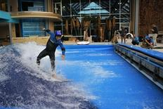Todd Holland, former professional surfer on the world tour, tests the waves on a surfboard at the still under-construction Surf's Up indoor water and surf park in Nashua, New Hampshire November 15, 2013. REUTERS/Brian Snyder