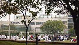 Unos empleados de Nokia realizan una protesta en una cancha de fútbol en las afueras de la planta de la firma en Dongguan, China, nov 20 2013. Trabajadores en huelga en una fábrica de Nokia en el sur de China amenazaron el viernes con continuar su medida de fuerza después de que la compañía decidió finalizar los contratos de 59 empleados por no volver a sus labores. REUTERS/James Pomfret