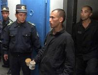 Охранники смотрят, как заключенные входят в тюрьму Жаслык, в 1.000 километрах в западу от Ташкента. Фото от 29 сентября 2003 года. Пытки в тюрьмах и полицейских участках остаются обыденным явлением в Узбекистане, где активисты и защитники прав человека подвергаются гонениям, сообщил в пятницу Комитет ООН против пыток. REUTERS/Shamil Zhumatov
