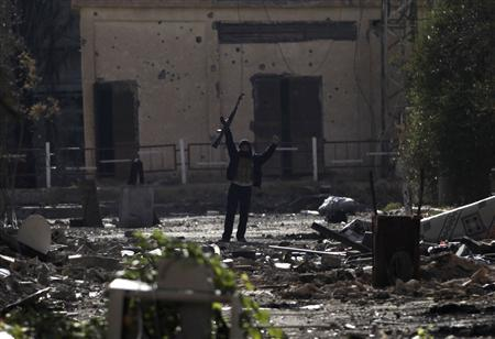 A Free Syrian Army fighter, standing on rubble, gestures as he holds up his weapon in Deir al-Zor, eastern Syria November 21, 2013. REUTERS/Khalil Ashawi
