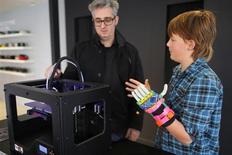 Leon McCarthy, de 12 años, (en la imagen a la derecha) habla sobre la impresora tridimesional MarkerBot Replicator 2, con el presidente ejecutivo de la compañía, Bre Pettis, en la nueva tienda de la firma en Boston, Massachusetts. 21 de noviembre, 2013. MakerBot, un fabricante de impresoras en tres dimensiones que abrió dos nuevas tiendas está semana, está entre las empresas que intentan llevar la innovadora tecnología de fabricación digital a los consumidores, pero los escépticos dicen que este despliegue es prematuro. REUTERS/Brian Snyder (ESTADOS UNIDOS - NEGOCIOS CIENCIA TECNOLOGIA)