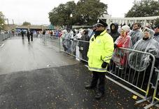 Dallas police officer John La Pietra stands in the middle of Elm Street where President John F. Kennedy was shot in 1963 as La Pietra and the crowd listen during ceremonies commemorating the 50th anniversary of the death of Kennedy in Dealey Plaza in Dallas, November 22, 2013. REUTERS/Jim Bourg