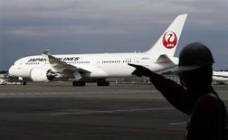 A staff of Japan Airlines' (JAL) walks past one of the company's Boeing Co's 787 Dreamliner plane at Narita international airport in Narita, east of Tokyo, November 11, 2013. REUTERS/Toru Hanai