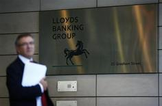 A man waits outside the corporate headquarters of Lloyds Banking Group in the City of London August 1, 2013. REUTERS/Andrew Winning