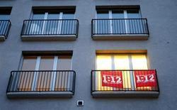 Salary initiative '1:12' flags are seen outside a window of an office of Swiss public workers union SSP in Zurich November 5, 2013. REUTERS/Arnd Wiegmann