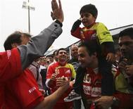 Felipe Massa carrega o filho nos ombros ao ser saudado por fãs após o GP Brasil de Fórmula 1, em Interlagos, São Paulo. 24/11/2013 REUTERS/Nacho Doce