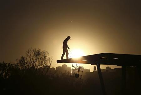 A construction worker stands on a rooftop near a residential compound in Kunming, Yunnan province, November 23, 2013. REUTERS/Wong Campion
