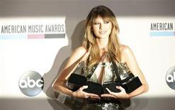 Cantora Taylor Swift posa para foto com as troféus que recebeu durante o 41º American Music Awards, em Los Angeles, Califórnia. A cantora country-pop Taylor Swift foi o destaque do American Music Awards, no domingo, levando para casa quatro troféus, inclusive o de artista do ano, numa cerimônia que reuniu alguns dos maiores nomes da música pop para a entrega de prêmios decididos pelos fãs. 24/11/2013. REUTERS/Mario Anzuoni