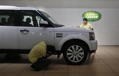 Showroom attendants polish a Land Rover vehicle at a Jaguar Land Rover showroom in Mumbai February 13, 2013. REUTERS/Vivek Prakash