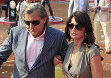 Gymnast Nadia Comaneci (R) and former tennis player Ilie Nastase of Romania leave the court after the awards ceremony at the Bucharest International tennis tournament in Bucharest September 25, 2011. REUTERS/Radu Sigheti