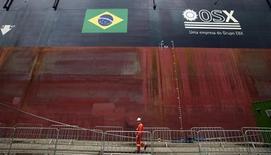Um funcionário anda em frente à FPSO OSX-1, a primeira unidade de produção, armazenagem e escoamento na frota da OSX, ancorada no porto do Rio de Janeiro. A empresa de construção naval teve prejuízo de 1,84 bilhão de reais no terceiro trimestre, revertendo o lucro de 6,92 milhões registrado um ano antes, informou a empresa do grupo do empresário Eike Batista na noite de segunda-feira. 17/11/2011 REUTERS/Sergio Moraes