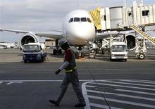 Um funcionário da Japan Airlines (JAL) passa por um dos Boeing 787 Demreanline no aeroporto internacional de Narita, ao leste de Tóquio. A Administração Federal de Aviação dos Estados Unidos (FAA, na sigla em inglês) irá orientar as empresas aéreas a evitar voos perto de tempestades com as aeronaves 787 Dreamliner e 747-8 da Boeing equipadas com motores da General Electric, após alguns aviões registrarem a formação de gelo no motor. 11/11/2013 REUTERS/Toru Hanai