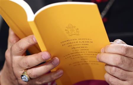 The document of the Evangelii Gaudium (The Joy of the Gospel) from Pope Francis is seen as Bishop Carlo Maria Celli reads during a presentation in Vatican November 26, 2013. REUTERS/Alessandro Bianchi