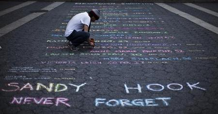 Street artist Mark Panzarino, 41, prepares a memorial as he writes the names of the Sandy Hook Elementary School victims during the six-month anniversary of the massacre, at Union Square in New York, June 14, 2013. REUTERS/Eduardo Munoz