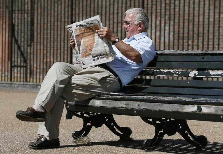 A man reads the Daily Mail newspaper featuring a picture of the newborn baby of Catherine, Duchess of Cambridge and Britain's Prince William, at Kensington Gardens in London July 24, 2013. REUTERS/Stefan Wermuth
