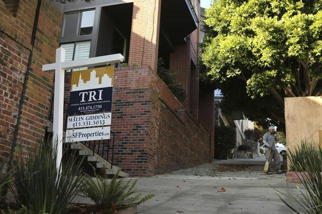 A man stands near a sign advertising a home for sale in the Pacific Heights neighborhood in San Francisco, California October 25, 2013. REUTERS/Robert Galbraith