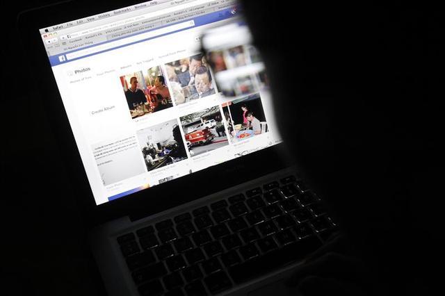 Vietnamese Internet activist Nguyen Lan Thang looks at a Facebook page at a cafe in Hanoi November 27, 2013. REUTERS/Kham