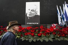 A man walks past the coffin of Israeli singer Arik Einstein, depicted in the placard, during a memorial ceremony before his funeral at Rabin square in Tel Aviv November 27, 2013. REUTERS/Nir Elias